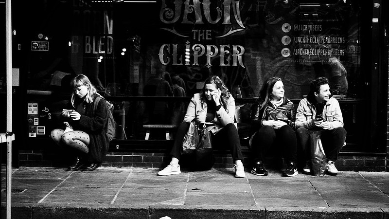 People sitting outside the hairdresser, Jack the Clipper, in London's Brick Lane