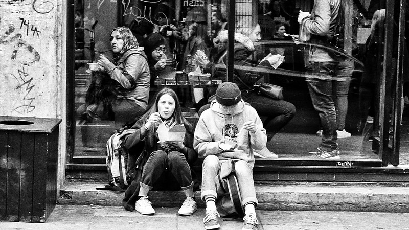 A couple eating food outside the Sunday Up Market in London's Brick Lane