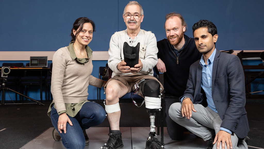 Man with prosthetic leg holding the liner, sitting next to the three researchers