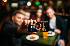 Fun friends makes selfie on phone in a sport bar