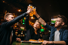 Fun company raised their glasses in a sport bar