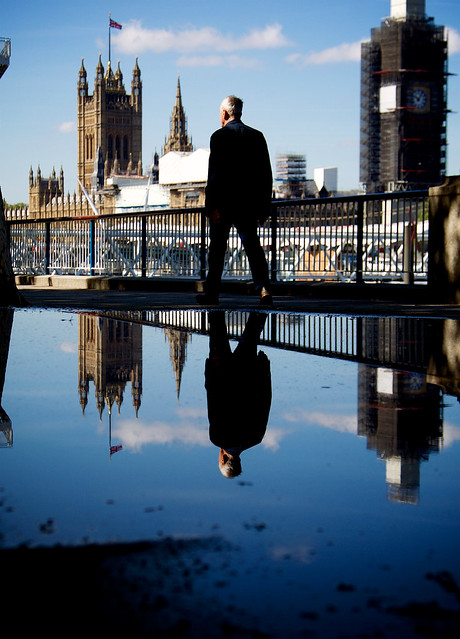 A man passing by Thames embankment with the British parliament under renovation in the background