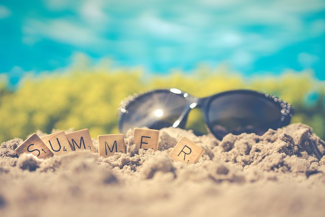 Sunglasses and the word summer spelled out in tiles on sand