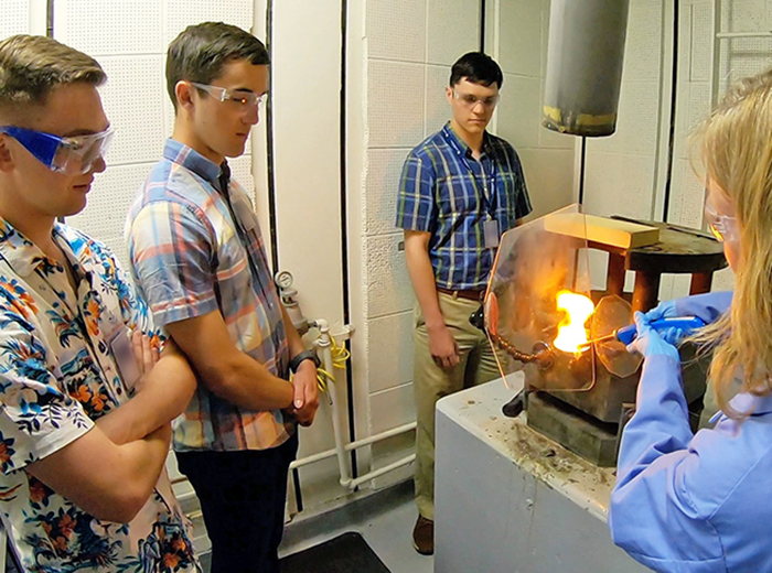 Three students watch as a scientist performs a demonstration about high explosives.