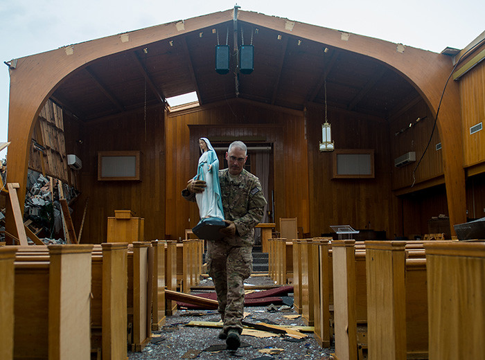A man carries a statue of the Virgin Mary down the aisle of a roofless chapel.