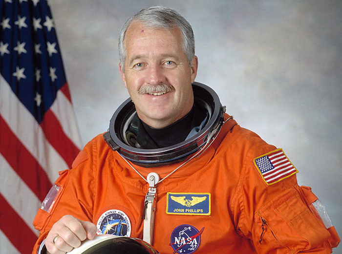 A man in a spacesuit poses for a photo; he is holding his helmet in his lap.