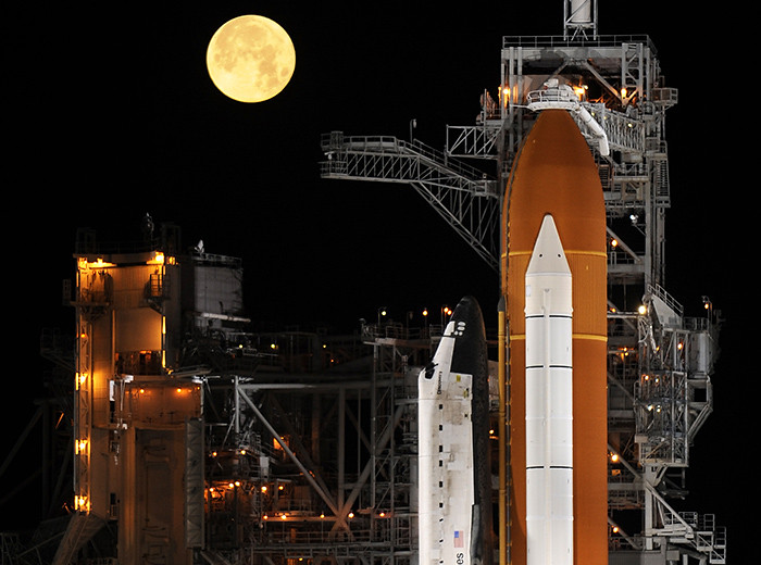 A full moon serves as a backdrop for a space shuttle sitting on the launchpad.