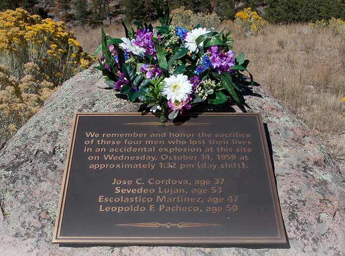 A plaque and a wreath of flowers on a rock.