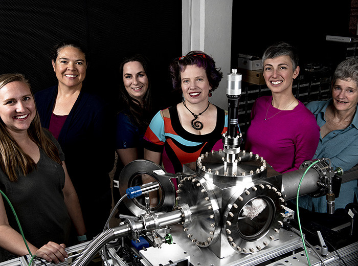 Six women stand behind a piece of equipment and pose for a picture.