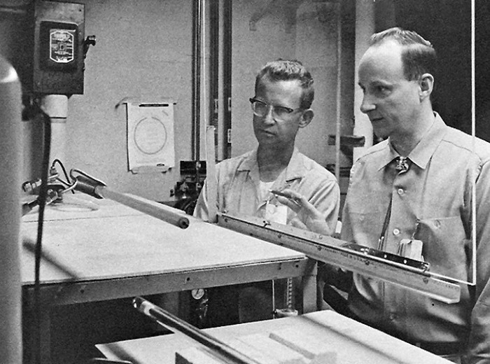 Black and white photo of two men looking at a heat pipe.