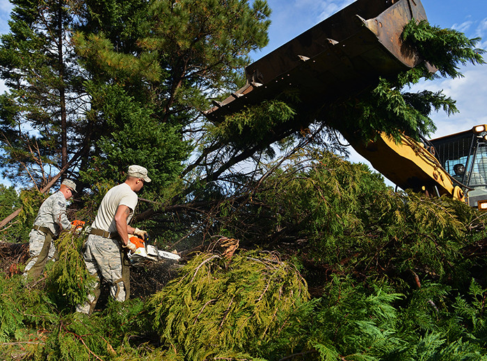 Two men cut through downed trees with chainsaws while a construction vehicle lifts tree limbs out of the way.