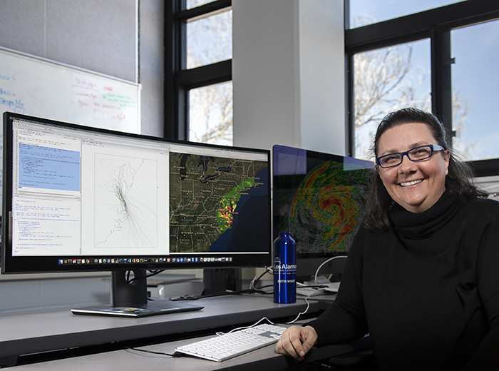 A woman sits in front of a computer screen that is displayinga map of the eastern United States.