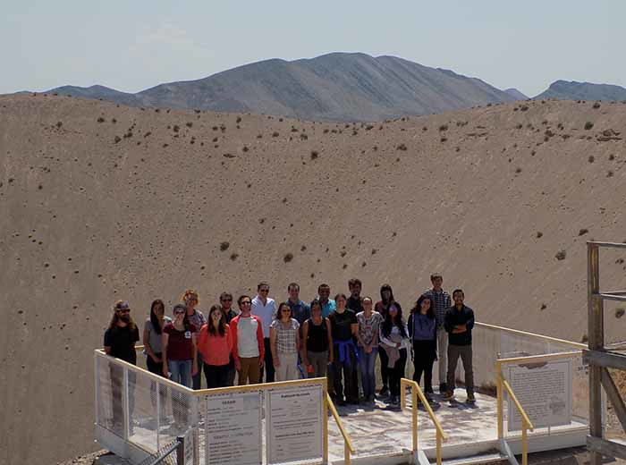 A group of people stand on a platform in front of a crater.