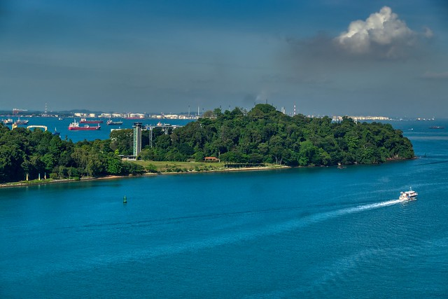 Sentosa island and ships in the roadstead seen from cable car coming from Mount Faber in Singapore