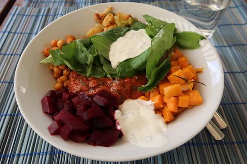 Bowl mit frischem Spinat, Joghurtsoße, Rote Beete Salat, Süßkartoffelwürfel, arabisch gewürzter Kichererbsen, Blumenkohlgemüse und würziger Tomatensoße