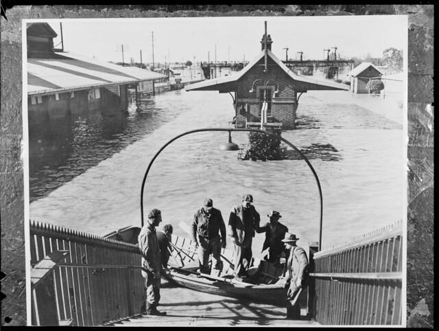 Flood Maitland Railway Station platforms covered men in boat, Maitland NSW