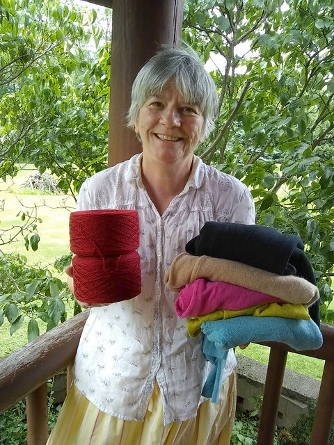 Simona Marian-Maloney of Recycled Yarn Co holding yarn and sweaters