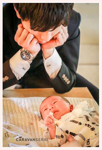 お宮参り 赤ちゃんを見つめるパパ