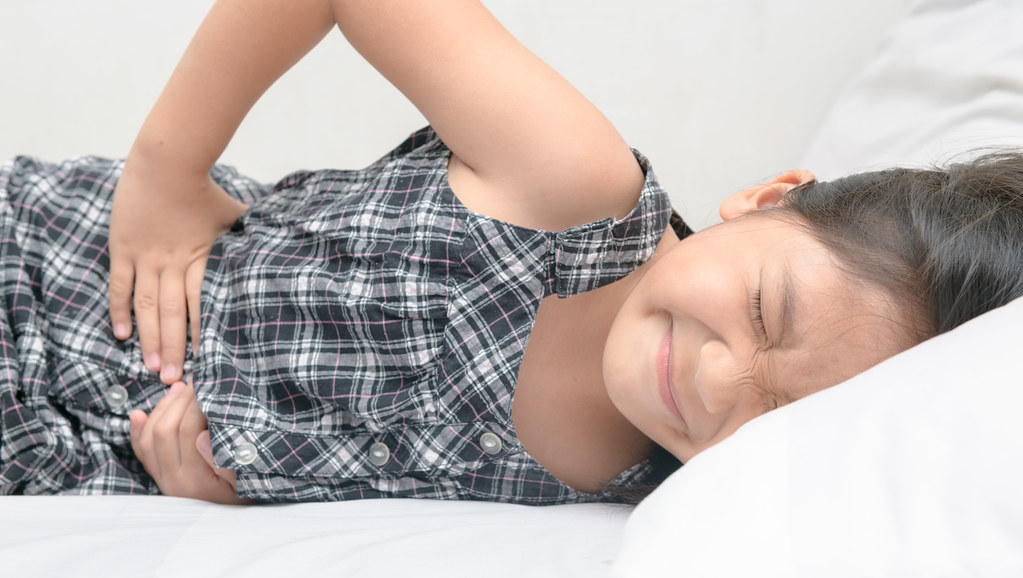 Child lying on bed clutching stomach in pain.