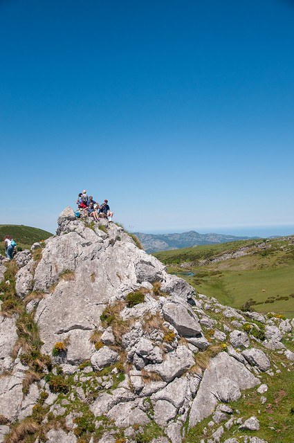 A group of people sit on a large stones at the top of a green mountain.