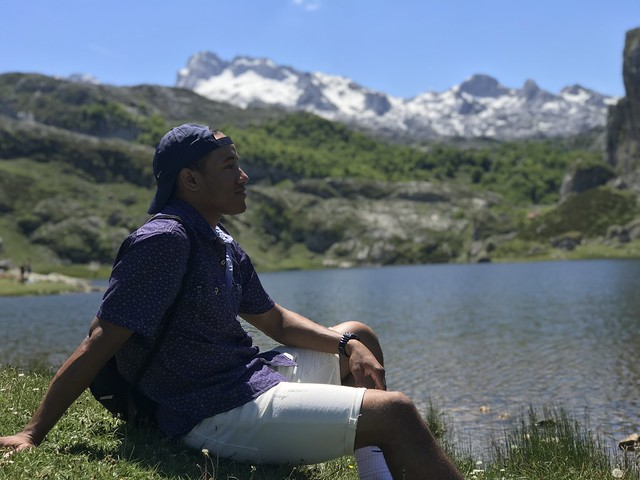 Portrait of a student sitting alongside a lake at the base of a mountain.