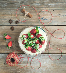 Rustic spicy ginger cake with cream-cheese filling and fresh strawberries with a rough wood background