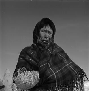 Inuit woman wearing a plaid shawl and smoking a pipe / Femme inuite portant un châle en tartan et fumant la pipe