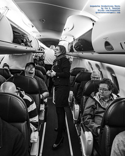 Flight Attendant Katie Helping 1st Class Passengers With Bags - B&W