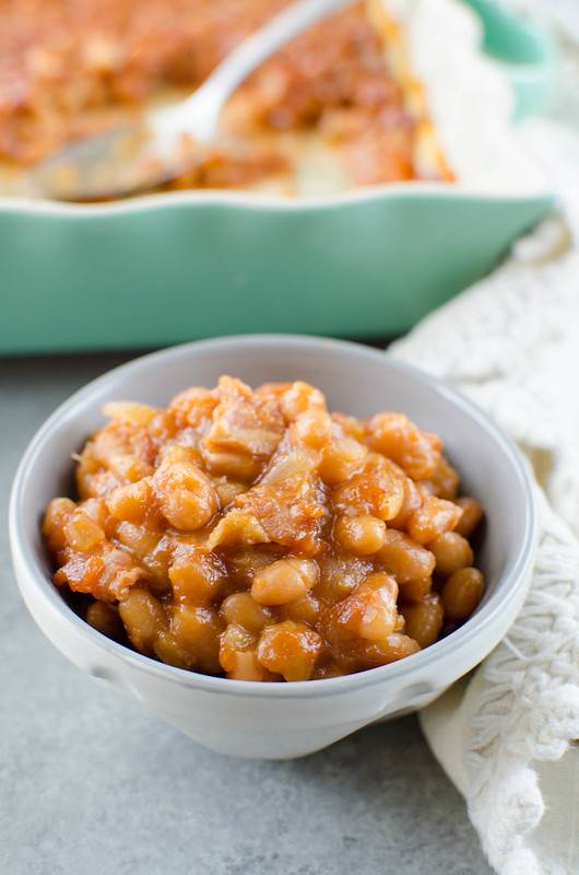 Pineapple Baked Beans - a favorite side dish for BBQs! Beans with bacon, crushed pineapple, and brown sugar are baked until the sauce is thick and delicious.