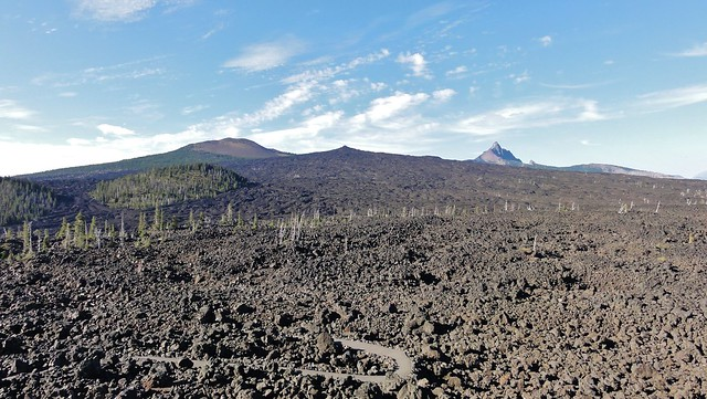 Black, rugged lava fields spread out from a variety of volcanoes: one is short and stubby, another short and weirdly pointy, and the highly eroded fins of an extinct volcano tower in the distance. There's a large round kipuka in the center-left where flows spared a bit of forest.