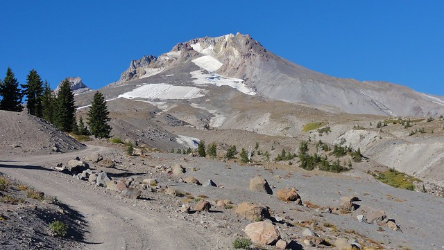 The summit of Mount Hood against a bright blue sky. Very little vegetation is able to grow in the loose tan volcanic rock and debris. A few snow patches cling to cliffs.