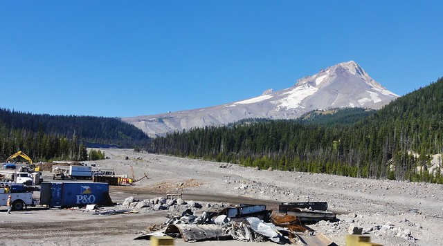 Construction equipment sits beside a wide, rock-strewn drainage emerging from Mount Hood, which rears in the distance.