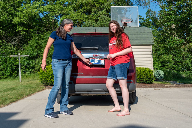 "Krissy and Athena pose in front of Athena's new car, to which the ""Not Cool"" plates are being attached."