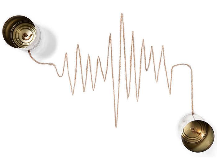 Two empty cans connected by a piece of string in the shape of a seismic reading.