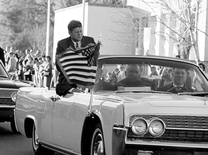 President Kennedy rides by the Los Alamos post office in a car.