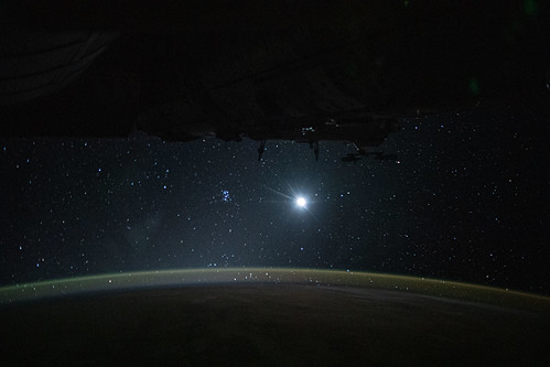 Earth's atmospheric glow, the Moon and a starry orbital nighttime background | by NASA Johnson