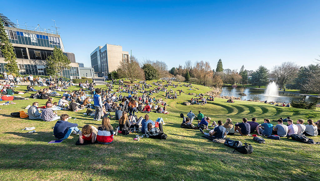 Students sitting on the grass around the lake.