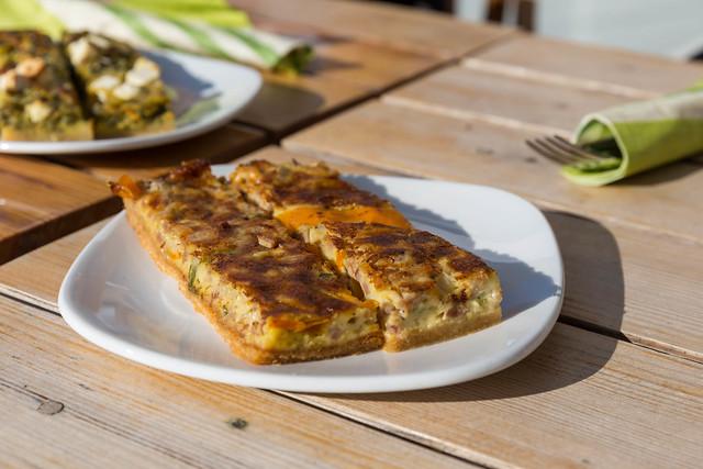 Finnisches Rührei-Omelett mit Käse und Gemüse, in Streifen geschnitten, auf einem weißen Frühstücksteller