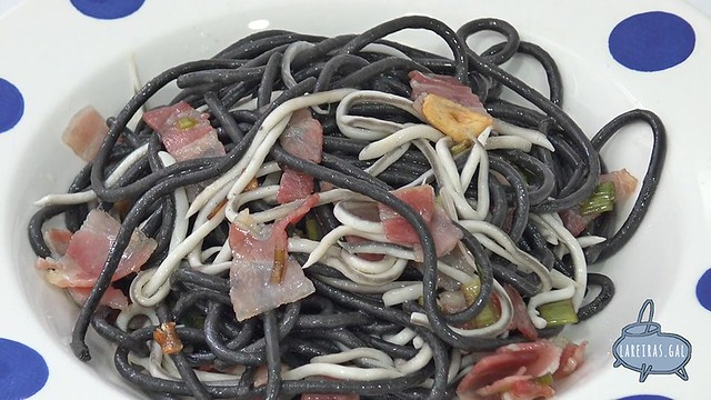 Salteado de espaguetis negros, beicon y gulas