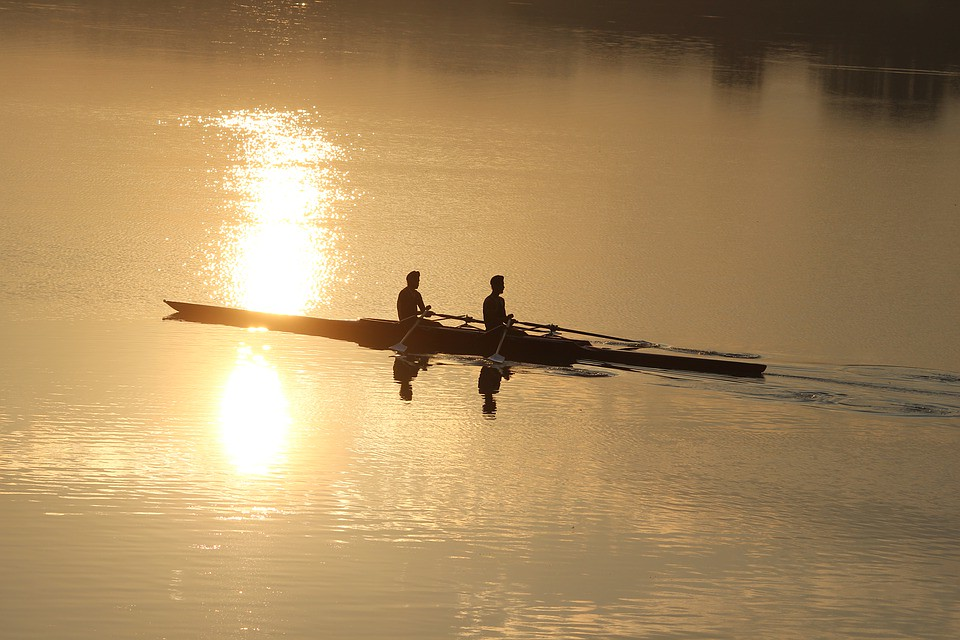 two people rowing with the sun rising