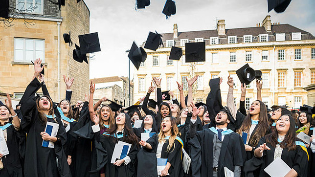 Students in graduation gowns throwing hats in the air