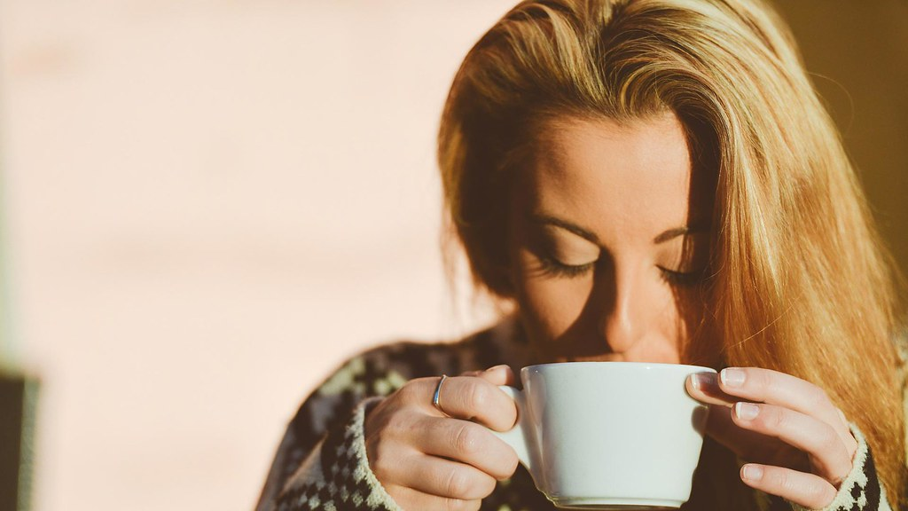 A woman drinking a cup of coffee carefully