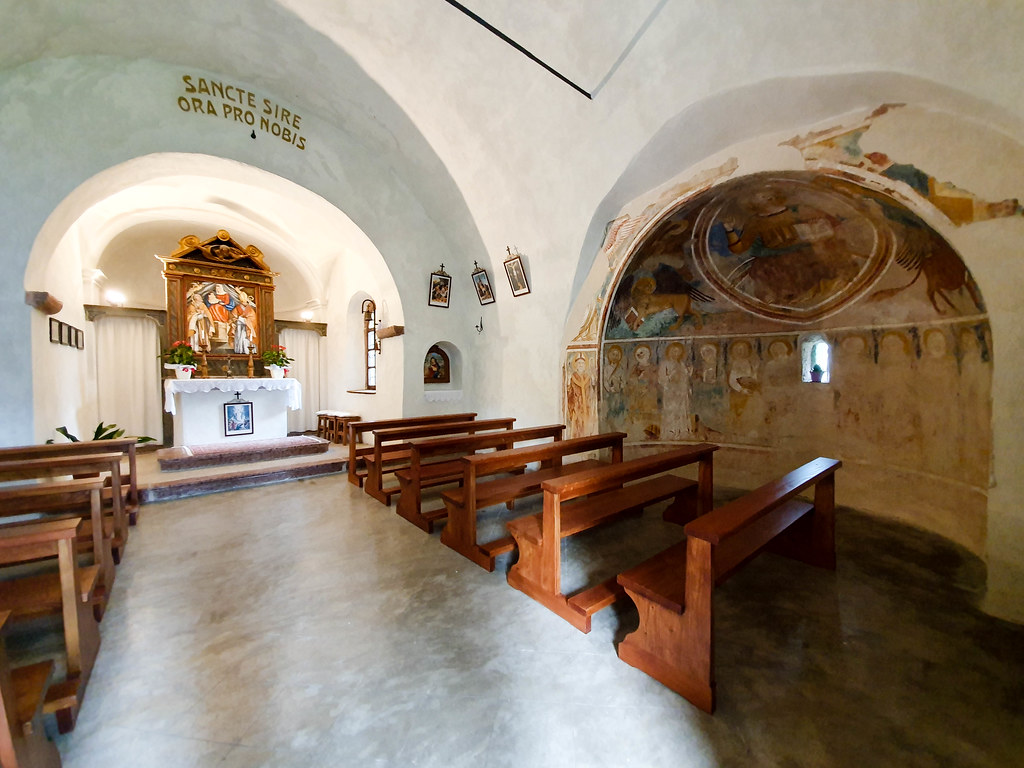 The interior of the small church, with the altar and the original wall paintings
