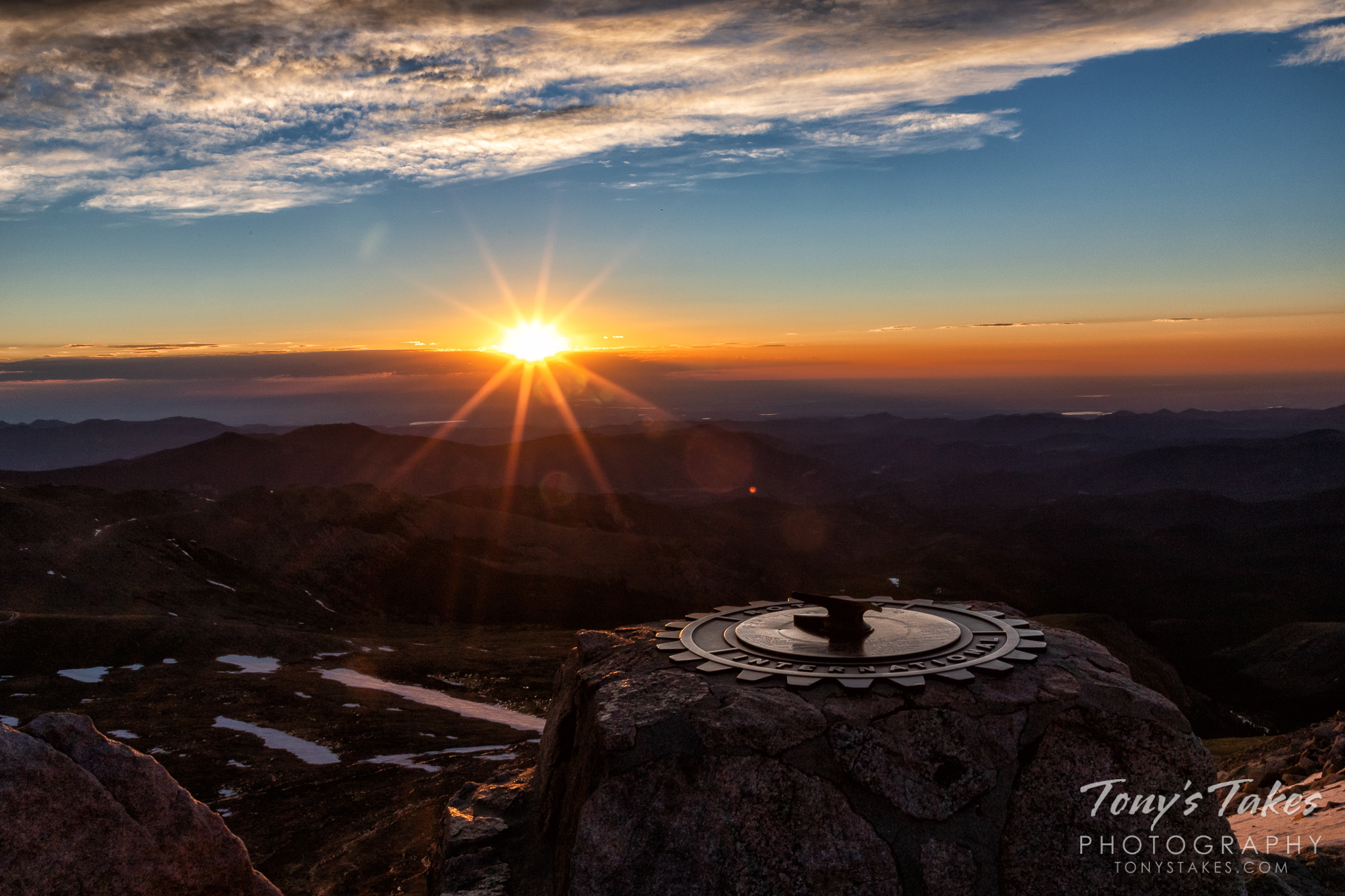 The sun rises over the horizon as seen from the top of Mount Evans in Colorado. (© Tony's Takes)