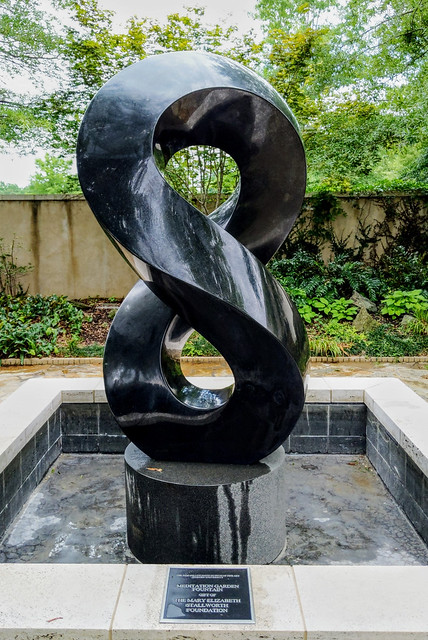 A seven-foot-tall black granite figure-8 sculpture stands on a pedestal in the Memorial Garden Fountain on the grounds of the Jule Collins Smith Museum of Fine Art.