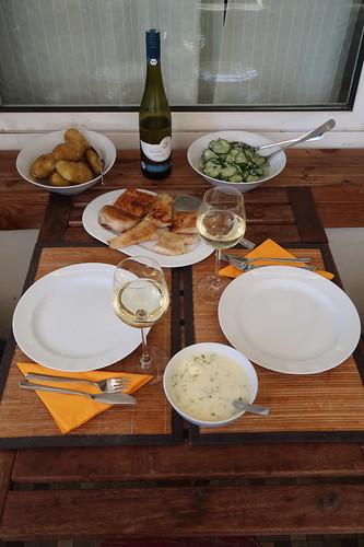 Mehliert gebratener Victoriasee-Barsch mit Weinsoße, neuen Kartoffeln und Gurkensalat (Tischbild)