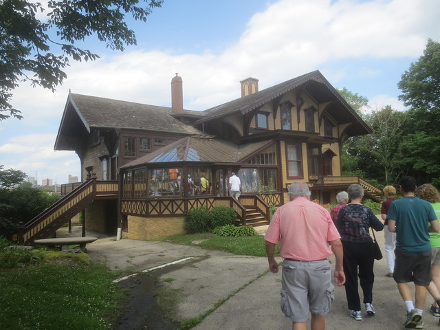 People walking toward a historic house built in Swiss cottage style