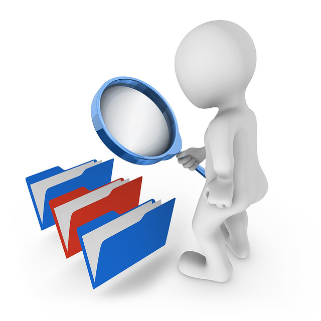 3d man with magnifying glass looks at folders. Choice concept.