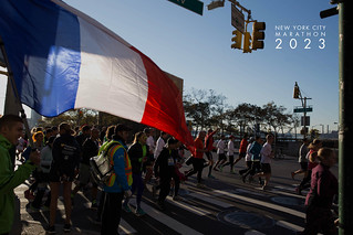Man holding a French Flag in front of athlete, next to picture title New York City Marathon 2023