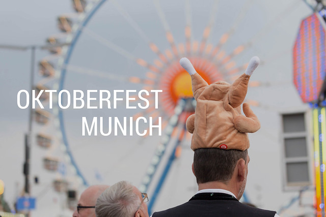 Man with a crazy, funny hat in front of a big ferris wheel at the Oktoberfest Munich